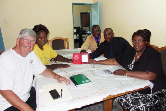 UMNS Photo: Charlie Moore (left) and staff at the Methodist Mission School in Murewa, Zimbabwe, pose with the school's first e-reader. Moore's church, Community UMC in Crofton, Maryland, is bringing 75 more e-readers to the school in March 2016.