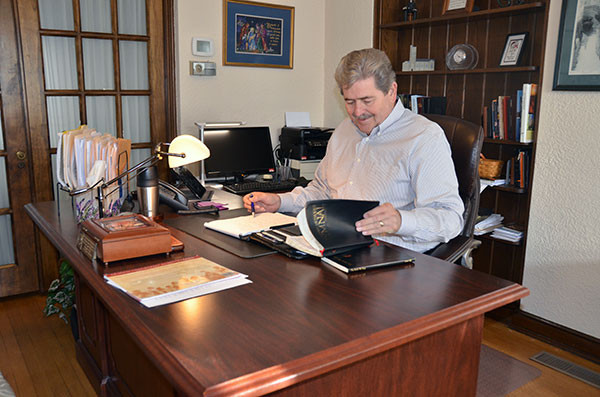 The Rev. David Simpson works at his desk in the office of Calvary UMC in Frederick.