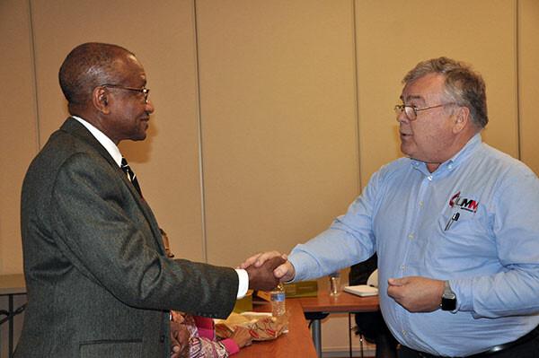 Bishop Marcus Matthews, left, receives a marble from Bill Weller.