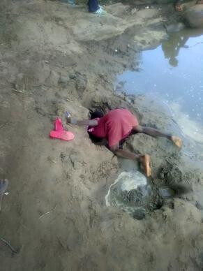 A girl burrows in the riverbed for water to drink. Dindi school children are risking their health and their lives drinking this unsafe water, which was their only option in March. Photo by Luckymore Mudzengerere, UMNS