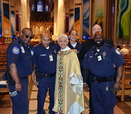 The Rev. Gina Campbell, center, stands with members of the Security Team at Washington National Cathedral on April 17. Campbell, who is the first non-Episcopalian to serve as worship director at the Cathedral, is leaving her post after 8 years.