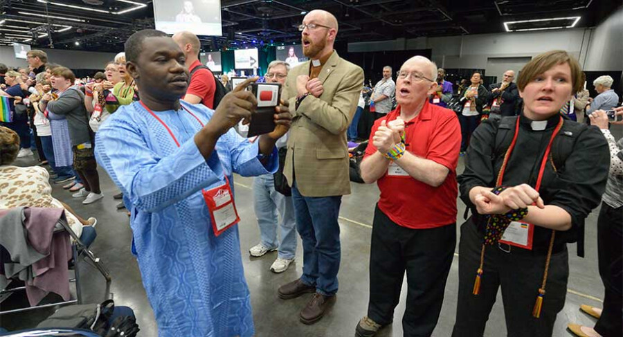 An African visitor uses his mobile phone to record protestors, their hands bound to protest the denomination's policies on human sexuality, as they demonstrate May 17 on the floor of the 2016 United Methodist General Conference in Portland, Ore. Photo by Paul Jeffrey, UMNS.