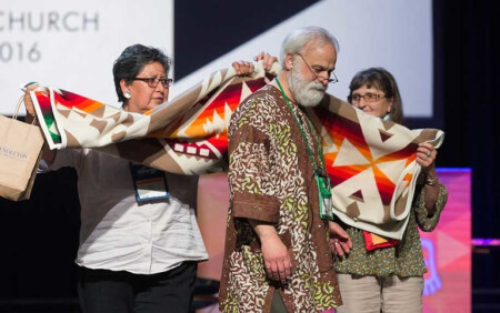 """The Rev. L. Fitzgerald """"Gere"""" Reist II (center) is honored for his years of service as secretary of the United Methodist General Conference during the denominational meeting May 20 in Portland, Ore. Presenting him with a blanket are Cynthia Kent (left) and Raggatha Calentine. Photo by Mike DuBose, UMNS."""