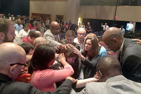 Clergy members surround T.C. Morrow in prayer following the vote not to commission her.