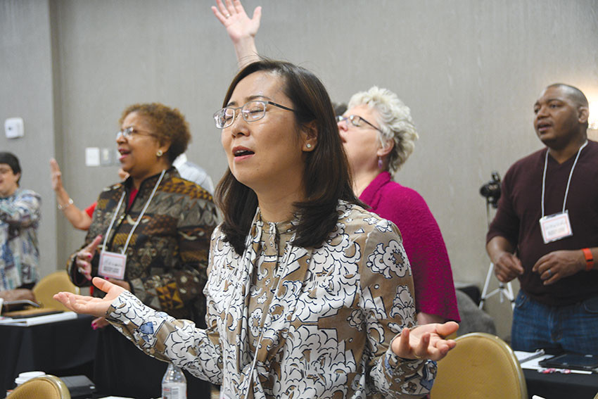 Pastor EunJoung Joo, of Washington Grove UMC, worships at the Multiethnic Church Conference in Oklahoma City March 30. Surrounding her are the Revs. Brenda Lewis, Laura Easto and George Winkfield. The two-day conference focused on becoming diversity-oriented so that the church can reflect the many faces of God.