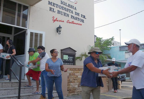 "A group of members and pastors from Methodist churches in the San Juan area form a human chain to unload supplies at the Utuado church in central Puerto Rico. The ""brigade"" drove into the area to help meet the needs of people who have not been reached by FEMA or federal aid organizations. Photo by the Rev. Gustavo Vasquez, UMNS."