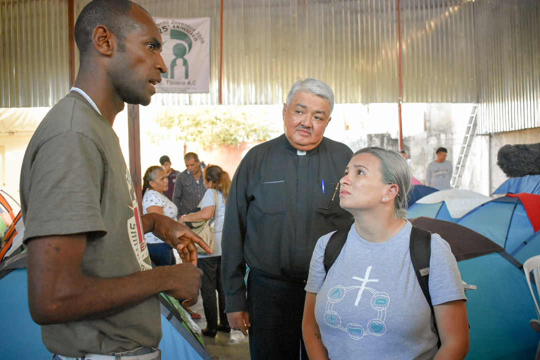 Emma Escobar and Rev Miguel Balderas from the BWC speaking to an assylum seeker at a migrant shelter full of tents in Tijuana