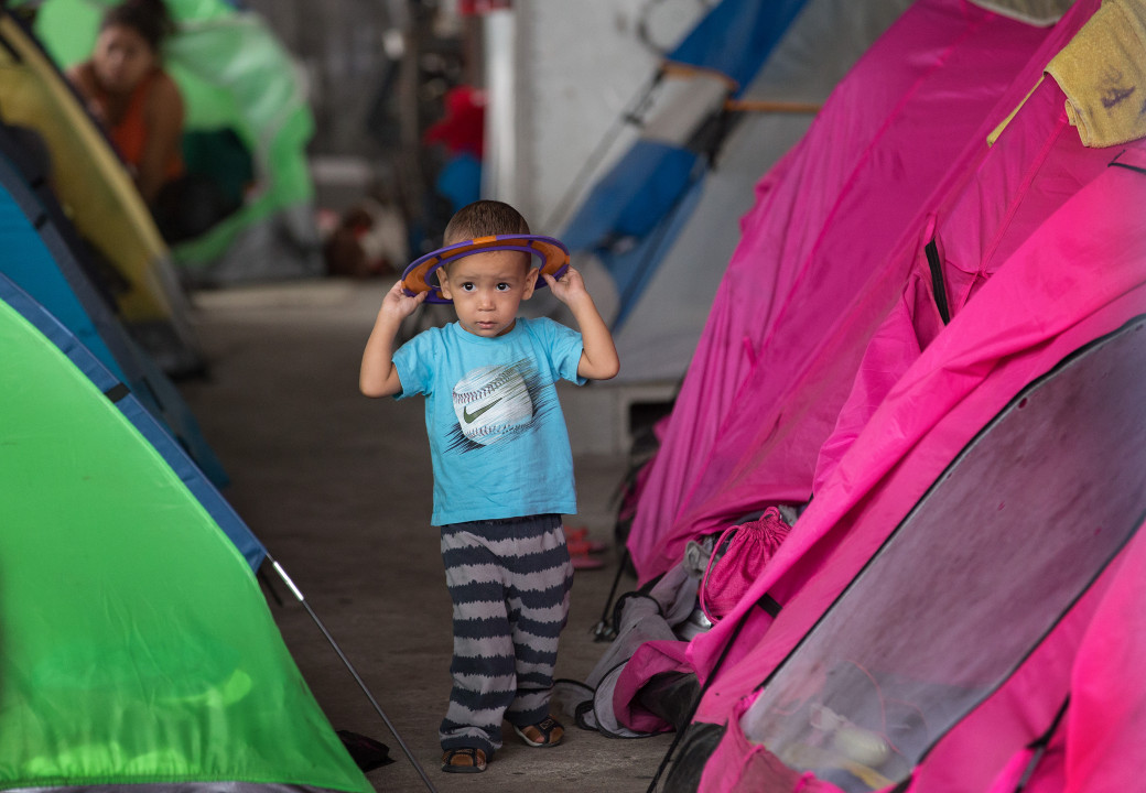 A child of an assylum seeker at a migration shelter full of tents in Tijuana